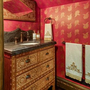Réalisation d'un WC et toilettes asiatique avec un placard en trompe-l'oeil, des portes de placard en bois brun, un mur rouge, un sol en bois foncé, un lavabo encastré, un sol marron et un plan de toilette noir.