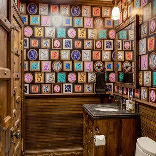 На фото: туалет в восточном стиле с темными деревянными фасадами, врезной раковиной и черной столешницей