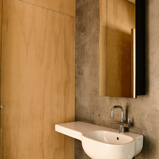 This is an example of a contemporary powder room in Melbourne with grey walls, mosaic tile floors, a wall-mount sink and black floor.