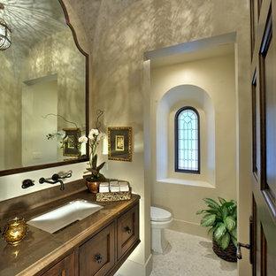 Cette photo montre un très grand WC et toilettes méditerranéen avec un placard avec porte à panneau encastré, des portes de placard en bois sombre, un WC à poser, un carrelage noir et blanc, un mur blanc, un sol en carrelage de terre cuite, un lavabo encastré, un plan de toilette en calcaire et un sol blanc.