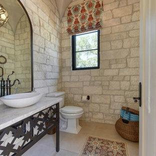 Immagine di un ampio bagno di servizio mediterraneo con consolle stile comò, WC a due pezzi, piastrelle beige, lastra di pietra, pareti bianche, pavimento in travertino, lavabo a bacinella, top in pietra calcarea, pavimento beige e top bianco