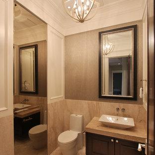 На фото: большой туалет в стиле фьюжн с настольной раковиной, фасадами с выступающей филенкой, темными деревянными фасадами, мраморной столешницей, унитазом-моноблоком, бежевой плиткой, плиткой из листового камня, бежевыми стенами, мраморным полом и бежевой столешницей с