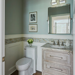 Small classic cloakroom in Baltimore with freestanding cabinets, grey cabinets, a one-piece toilet, multi-coloured tiles, glass tiles, blue walls, medium hardwood flooring, a submerged sink, laminate worktops and brown floors.