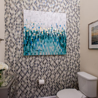 This is an example of a small traditional cloakroom in Jacksonville with a one-piece toilet, multi-coloured tiles, glass sheet walls, beige walls and a pedestal sink.