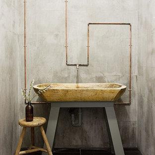 Esempio di un bagno di servizio industriale di medie dimensioni con top in pietra calcarea, piastrelle nere, piastrelle in pietra e lavabo rettangolare