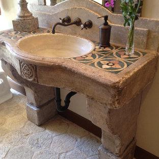 Immagine di un bagno di servizio mediterraneo di medie dimensioni con piastrelle multicolore, pavimento in pietra calcarea, lavabo a consolle e top in pietra calcarea