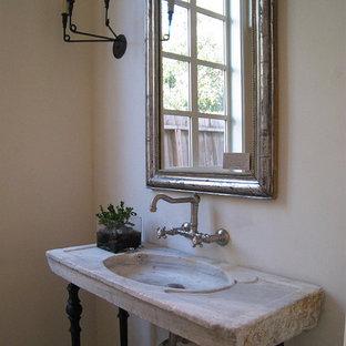 Esempio di un bagno di servizio mediterraneo di medie dimensioni con pavimento in pietra calcarea, lavabo a consolle e top in pietra calcarea
