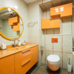 Ejemplo de aseo contemporáneo con armarios con paneles lisos, puertas de armario naranjas, encimera de vidrio, sanitario de pared, baldosas y/o azulejos beige y encimeras naranjas