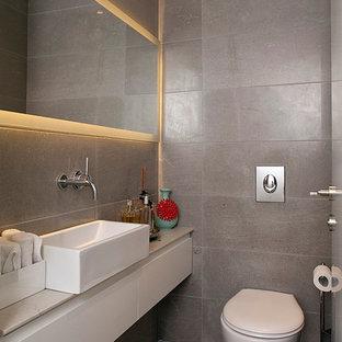 Idée de décoration pour un WC et toilettes design de taille moyenne avec un placard à porte plane, des portes de placard blanches, un WC suspendu, un carrelage gris, un sol en calcaire, du carrelage en pierre calcaire et une vasque.