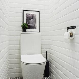 Неиссякаемый источник вдохновения для домашнего уюта: туалет в скандинавском стиле с унитазом-моноблоком, полом из керамической плитки, белой плиткой, плиткой кабанчик и разноцветным полом
