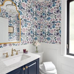 Exemple d'un petit WC et toilettes chic avec un placard avec porte à panneau encastré, des portes de placard bleues, un WC séparé, un sol en carrelage de terre cuite, un lavabo encastré, un plan de toilette en quartz modifié, un sol blanc, un plan de toilette blanc et un mur multicolore.