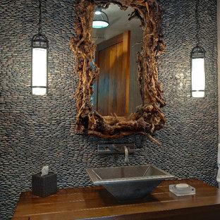 アトランタのラスティックスタイルのおしゃれなトイレ・洗面所 (ベッセル式洗面器、木製洗面台、石タイル、ブラウンの洗面カウンター) の写真