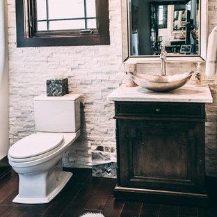 На фото: туалеты в стиле рустика с фасадами с утопленной филенкой, темными деревянными фасадами, раздельным унитазом, белой плиткой, каменной плиткой, бежевыми стенами, полом из ламината, настольной раковиной, столешницей из гранита, коричневым полом и белой столешницей