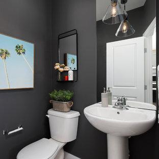 Свежая идея для дизайна: маленький туалет в стиле современная классика с черными стенами, полом из ламината, раковиной с пьедесталом, раздельным унитазом и коричневым полом - отличное фото интерьера