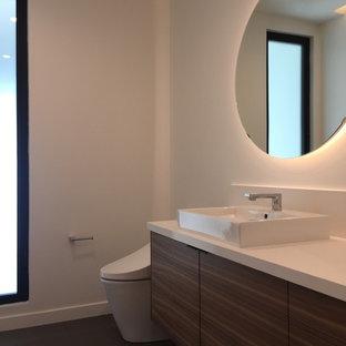 Aménagement d'un WC et toilettes moderne de taille moyenne avec un placard à porte plane, des portes de placard en bois brun, un bidet, un carrelage blanc, un mur blanc, un sol en carrelage de porcelaine, une vasque, un plan de toilette en quartz modifié, un sol gris et un plan de toilette blanc.