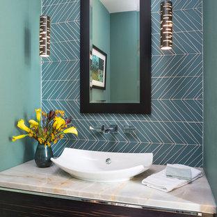デンバーのコンテンポラリースタイルのおしゃれなトイレ・洗面所 (フラットパネル扉のキャビネット、濃色木目調キャビネット、男性用トイレ、青いタイル、ガラスタイル、青い壁、無垢フローリング、ベッセル式洗面器、茶色い床、グレーの洗面カウンター) の写真