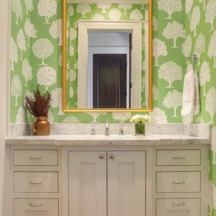 Idée de décoration pour un WC et toilettes tradition avec un placard à porte affleurante, des portes de placard blanches, un plan de toilette en marbre et un mur vert.