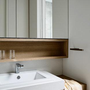 Неиссякаемый источник вдохновения для домашнего уюта: большой туалет в современном стиле с открытыми фасадами, фасадами цвета дерева среднего тона, унитазом-моноблоком, серыми стенами, паркетным полом среднего тона, накладной раковиной, столешницей из ламината, коричневым полом и коричневой столешницей