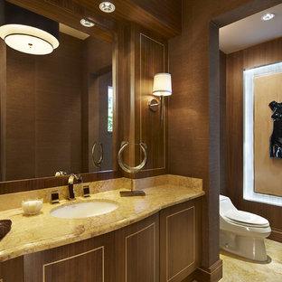 Bild på ett mellanstort funkis gul gult toalett, med möbel-liknande, en toalettstol med hel cisternkåpa, gul kakel, stenhäll, bruna väggar, marmorgolv, granitbänkskiva, skåp i mörkt trä och ett undermonterad handfat