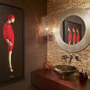 Стильный дизайн: маленький туалет в современном стиле с коричневыми стенами, настольной раковиной, столешницей из дерева, коричневой плиткой и красной столешницей - последний тренд