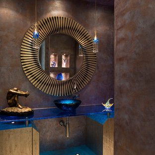 Пример оригинального дизайна: туалет в современном стиле с настольной раковиной, стеклянной столешницей и синей столешницей