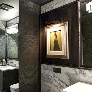 Cette photo montre un petit WC et toilettes moderne avec un placard à porte plane, des portes de placard en bois sombre, un WC suspendu, un carrelage blanc, du carrelage en marbre, un mur noir, un sol en marbre, un lavabo encastré, un plan de toilette en quartz modifié et un sol blanc.
