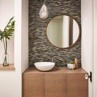 Стильный дизайн: туалет в современном стиле с зеленой плиткой, стеклянной плиткой, белыми стенами, паркетным полом среднего тона, настольной раковиной, столешницей из дерева, коричневым полом и коричневой столешницей - последний тренд