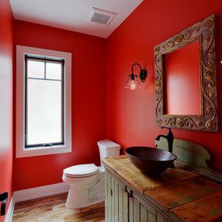 Cette photo montre un WC et toilettes craftsman de taille moyenne avec un mur rouge, un placard à porte persienne, des portes de placard en bois vieilli, un WC séparé, un sol en bois clair, une vasque, un plan de toilette en bois et un plan de toilette marron.
