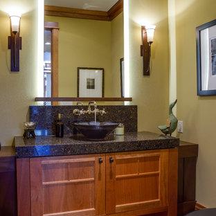 Modelo de aseo de estilo americano con lavabo sobreencimera, armarios con paneles empotrados, puertas de armario de madera oscura, paredes beige y encimeras negras
