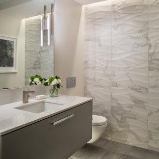 Ejemplo de aseo contemporáneo con armarios con paneles lisos, puertas de armario grises, baldosas y/o azulejos multicolor, paredes beige, lavabo bajoencimera, suelo gris y encimeras blancas