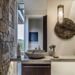 Свежая идея для дизайна: туалет в современном стиле с плоскими фасадами, темными деревянными фасадами, бежевыми стенами, настольной раковиной, серым полом и серой столешницей - отличное фото интерьера