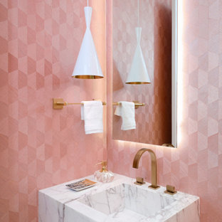 Contemporary powder room in Miami with pink walls, an integrated sink and white benchtops.