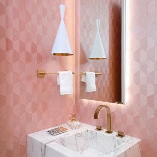 Moderne Gästetoilette mit rosa Wandfarbe, integriertem Waschbecken und weißer Waschtischplatte in Miami