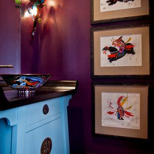 Imagen de aseo de estilo zen con lavabo sobreencimera, puertas de armario azules, encimera de madera y paredes púrpuras