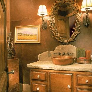 Mittelgroße Urige Gästetoilette mit Aufsatzwaschbecken, hellbraunen Holzschränken, dunklem Holzboden, profilierten Schrankfronten, brauner Wandfarbe und beiger Waschtischplatte in Denver
