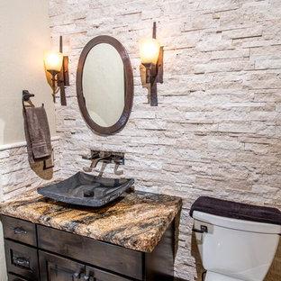 Неиссякаемый источник вдохновения для домашнего уюта: большой туалет в стиле рустика с настольной раковиной, фасадами с выступающей филенкой, темными деревянными фасадами, столешницей из гранита, унитазом-моноблоком, бежевой плиткой, каменной плиткой, бежевыми стенами и полом из травертина