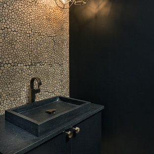 Cette photo montre un petit WC et toilettes tendance avec un placard à porte plane, des portes de placard noires, un carrelage beige, carrelage en mosaïque, un mur noir, un sol en bois clair, une vasque, un plan de toilette en stéatite, un sol beige et un plan de toilette noir.