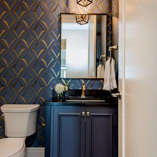 Idées déco pour un petit WC et toilettes classique avec un placard avec porte à panneau encastré, des portes de placard bleues, un mur bleu, un sol en bois foncé, un lavabo encastré, un plan de toilette en granite, un sol marron, un plan de toilette noir et un WC séparé.
