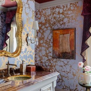 Aménagement d'un WC et toilettes classique avec un placard à porte plane, des portes de placard beiges, un mur violet, un lavabo encastré, un sol marron et un plan de toilette marron.