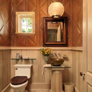Inspiration pour un WC et toilettes rustique avec une vasque, un plan de toilette en verre, un WC séparé, un mur marron et un sol en bois clair.