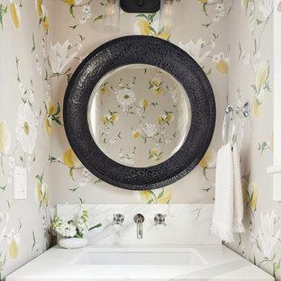 Idée de décoration pour un WC et toilettes tradition avec un placard avec porte à panneau encastré, des portes de placard grises, un mur multicolore, un lavabo encastré, un plan de toilette blanc, meuble-lavabo encastré et du papier peint.