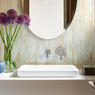 This is an example of a small modern cloakroom in Atlanta with a one-piece toilet, multi-coloured tiles, mosaic tiles, white walls, porcelain flooring, a vessel sink, engineered stone worktops, grey floors, beige cabinets and beige worktops.