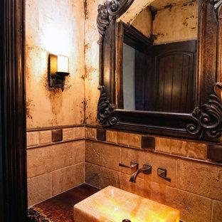 Идея дизайна: большой туалет в средиземноморском стиле с фасадами островного типа, коричневыми фасадами, унитазом-моноблоком, полом из травертина, настольной раковиной, столешницей из дерева, разноцветной плиткой, каменной плиткой, разноцветными стенами и разноцветным полом