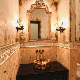 Photo of a large mediterranean cloakroom in Austin with freestanding cabinets, brown cabinets, a one-piece toilet, travertine flooring, a vessel sink, wooden worktops, multi-coloured tiles, stone tiles, multi-coloured walls and multi-coloured floors.