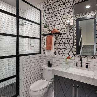 Inredning av ett klassiskt litet vit vitt toalett, med vit kakel, keramikplattor, marmorgolv, ett undermonterad handfat, marmorbänkskiva, vitt golv, luckor med infälld panel, svarta skåp, en toalettstol med separat cisternkåpa och flerfärgade väggar