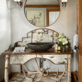 Cette photo montre un WC et toilettes montagne de taille moyenne avec un mur gris, un sol en bois brun, une vasque, un plan de toilette en bois, un sol marron, un plan de toilette marron, meuble-lavabo sur pied, un plafond en papier peint et du papier peint.