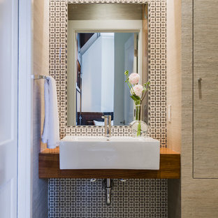 Small contemporary cloakroom in Boston with a vessel sink, wooden worktops, multi-coloured tiles, medium wood cabinets, ceramic tiles, beige walls, mosaic tile flooring, grey floors and brown worktops.