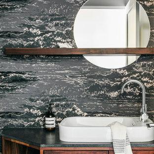 Foto på ett litet funkis svart toalett, med släta luckor, skåp i mellenmörkt trä, ett fristående handfat, blå väggar och granitbänkskiva