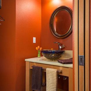 На фото: маленький туалет в стиле модернизм с фасадами островного типа, фасадами цвета дерева среднего тона, белой плиткой, бетонным полом, настольной раковиной и оранжевыми стенами