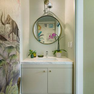 Idée de décoration pour un petit WC et toilettes design avec un lavabo encastré, un placard à porte plane, des portes de placards vertess, un plan de toilette en marbre, béton au sol, un mur beige et un plan de toilette blanc.